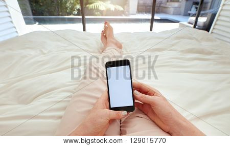 Woman Using Smart Phone On Bed