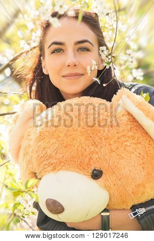 pretty girl with teddy bear in spring flowers