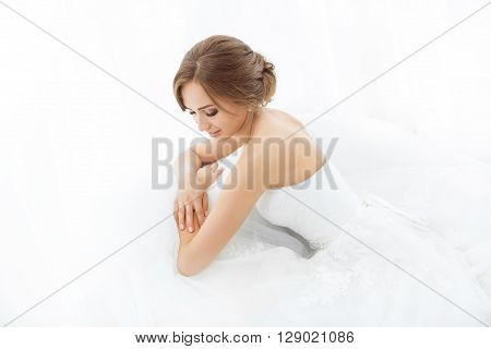 Beautiful young bride portrait in white wedding dress indoors.  Luxuty model sitting against big window at home. Girl waiting her groom in bright room. Beautiful wedding hairdress. High key photo.