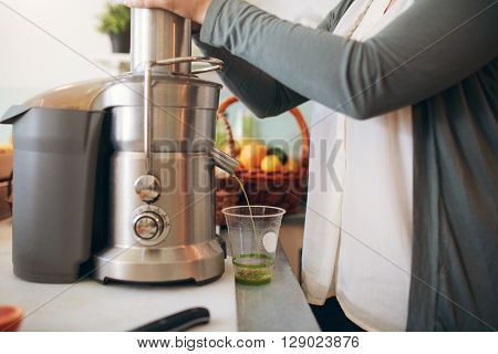 Woman Making Fruit Juice Using Juicer