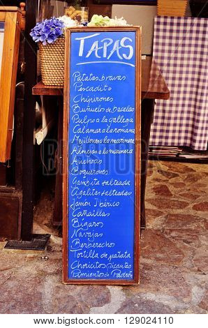 the chalkboard menu in a restaurant in Spain, with different spanish tapas, such as patatas bravas or tortilla de patatas