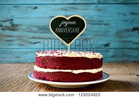 a red velvet cake with a heart-shaped chalkboard with the text joyeux anniversaire, happy birthday in french, on a rustic wooden table