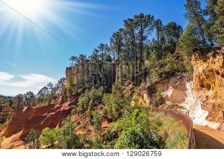 Beautiful and striking contrast between the green pine trees and yellow ocher soil. Unique red and orange hills in the province of Languedoc - Roussillon, France