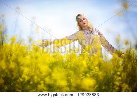 Beautiful woman in oilseed rape flowers, yellow field