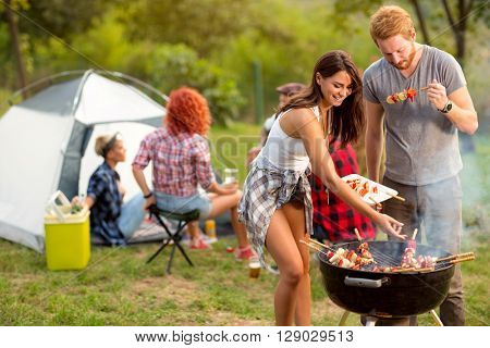 Young brunette with boyfriend serving on plate barbecue to their friends in campground
