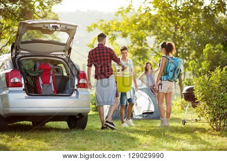 friends unpacking car for camping trip in countryside