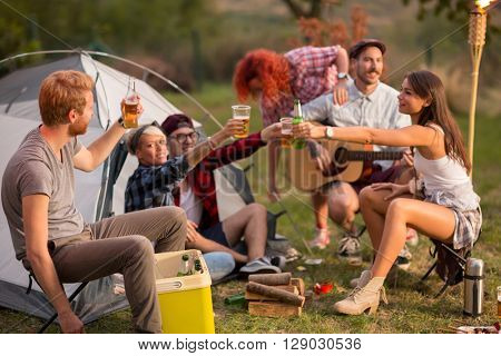 Young group toasting with bottles and glasses of beer in campground on sunset in forest
