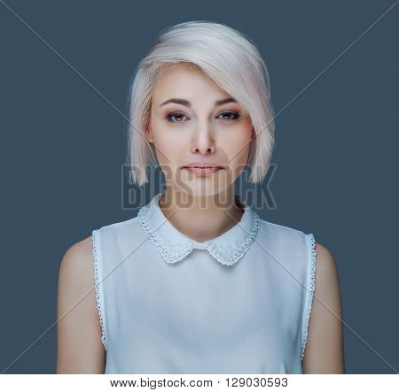 humorous portrait of a young unhappy woman isolated against gray background