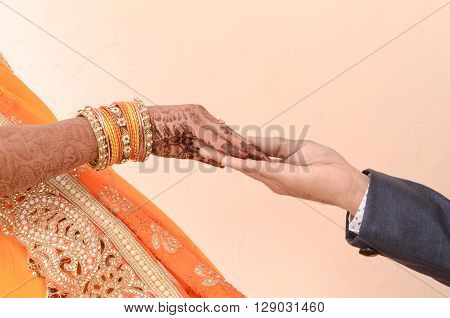bride and groom joining hands during an Indian wedding ritual