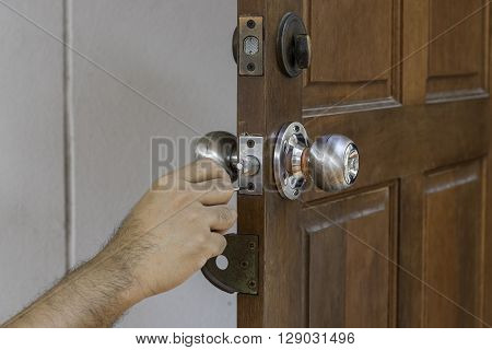 hand of man and locksmith on old wood door