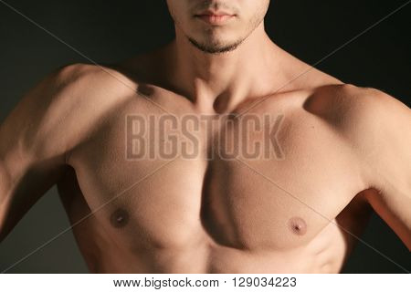 Torso of a well built man's pectoral on black background