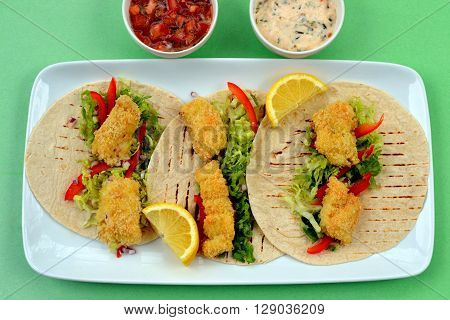 Fish Tacos - Pieces of fried panko encrusted haddock with shredded lettuce, red onion, red pepper slices and lemon wedges on round flour tortillas. Tomato Salsa and Cilantro sauce in small white bowls on the side.