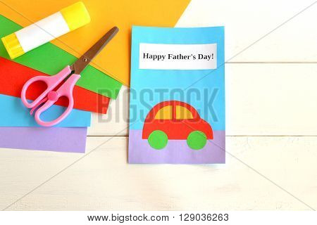 Greeting card father's day. Happy father's day. Kids crafts. Paper sheets, scissors, glue on white wooden background