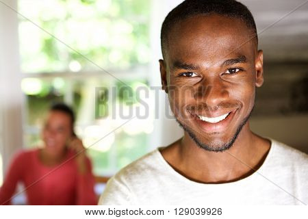 Handsome African Man Smiling With A Woman In Background