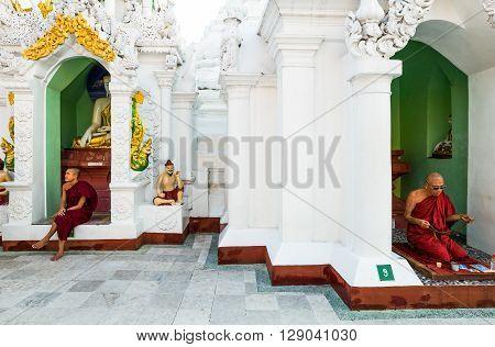 Yangon Myanmar - January 9 2012: Monks seated in front of Buddha shrines in the Swedagon Pagoda.