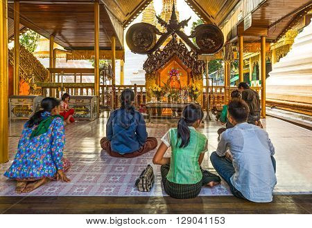 Yangon Myanmar - January 9 2012: Local religious in prayer in the Swedagon Pagoda.