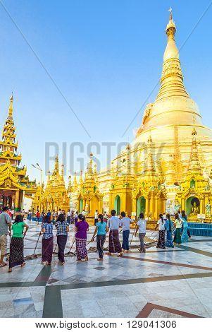 Yangon Myanmar - January 9 2012: Young local religious cleaning the floor of the Swedagon Pagoda.