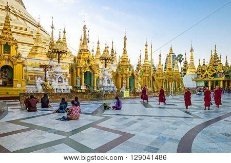 Yangon Myanmar - January 9 2012: Religious in prayer and monks in the Swedagon Pagoda.