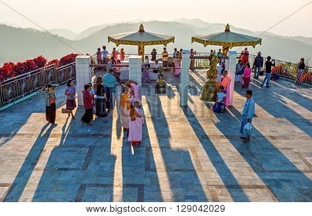 Kyaikhto Myanmar - January 10 2012: People and monks on a terrace of the sacred Buddhist mountain of Kyaikhto