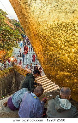 Kyaikhto Myanmar - January 10 2012: Religious in prayer under the delicately balanced golden Stupa on the sacred Buddhist mountain