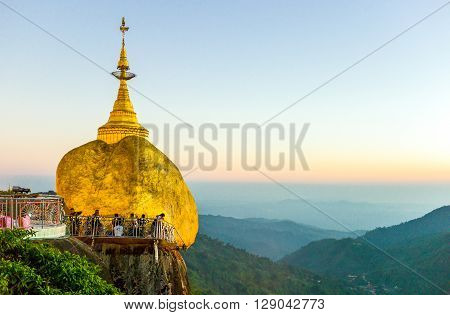 Kyaikhto Myanmar - January 10 2012: Local people under the delicately balanced golden Stupa on the sacred Buddhist mountain