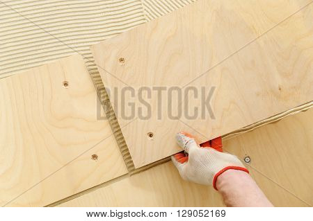 Laying plywood on the floor. The worker put a piece of plywood on the floor with glue.