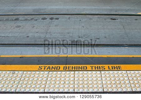 Closeup of tramway with yellow signage ?STAND BEHIND THIS LINE? on concrete road at the tram stop in Melbourne, Australia