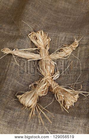 Close up of a raffia doll on a burlap fabric