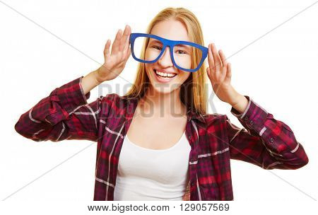 Happy blonde woman holding fake glasses in front of her eyes