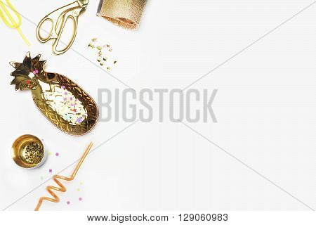 Gold woman items on table. Feminine scene glamour style. White background mock up. Flat lay party desk. Table view workspace. Pineapple gold handbag Golden shears confetti. Product mockup