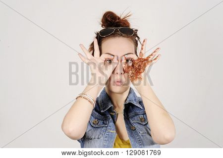 Funny attractive and trendy hipster girl clowning, happy lifestyle concept . Studio shot with grey background.