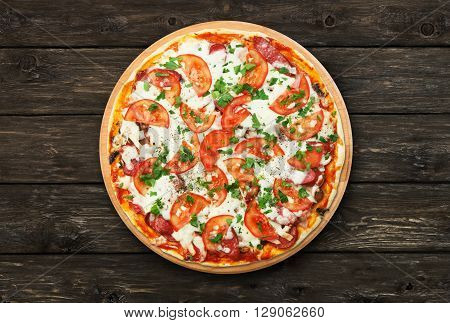 Delicious pizza with mushrooms, tomatoes and chicken ham - thin pastry crust at wooden round desk and rustic wood background. Italian food. Top view