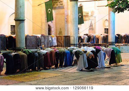 SARAJEVO BOSNIA AND HERZEGOVINA - SEPTEMBER 3 2009: Segregated muslims bowing in Isha prayer at Gazi Husrev-beg mosque