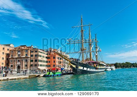 VENICE, ITALY - 17 OCTOBER 2015: The Palinuro, a historic Italian Navy training barquentine, moored in the Giudecca Canal, Venice, Italy in front of historic waterfront palazzi. October 17 2015.