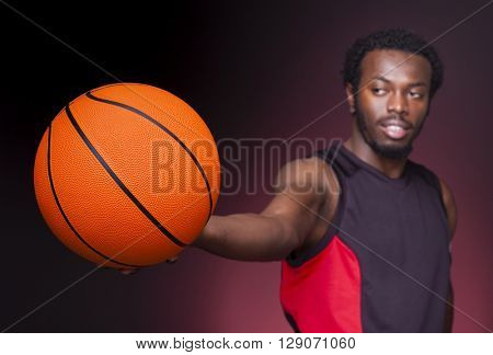Afro american basketball player holding a ball on dark background