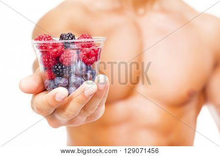 Close-up of a fit man holding a bowl of fresh red fruits, isolated on white background