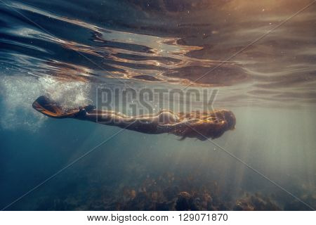 Attractive young woman floating in beautiful ethereal swimming pool