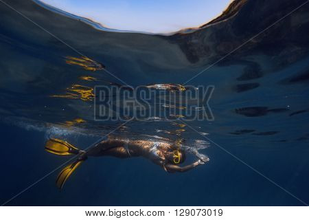 Woman floating underwater in mask
