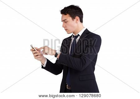 A young Caucasian business man is frowning holding a moble phone. He is operating the smart phone with fingers on the screen.