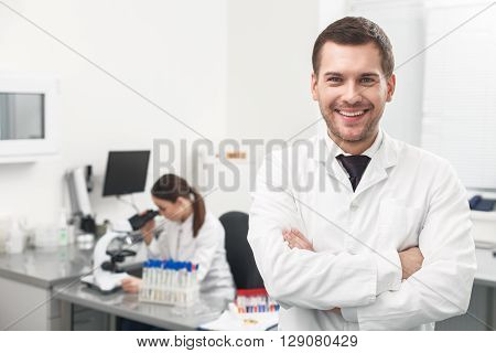 Portrait of attractive young scientist standing and smiling. Man is looking forward happily. His female assistant is working with microscope on background
