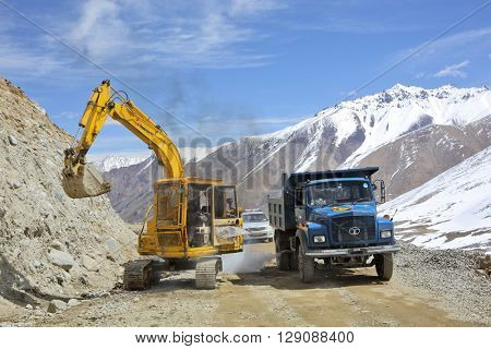 KHARDUNG LA PASS, INDIA - APRIL 21, 2016: Road construction at Kardung La one of th highest motorable road (5360 m) in the world. The pass is strategically important to India
