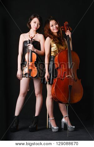 Two young woman is playing the violin-black background