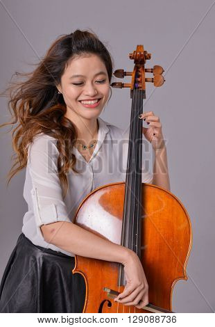 Young violin player isolated on gray