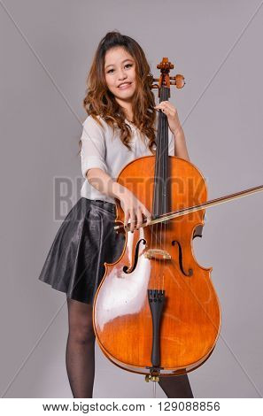 Elegant girl playing big violin, studio isolated shot