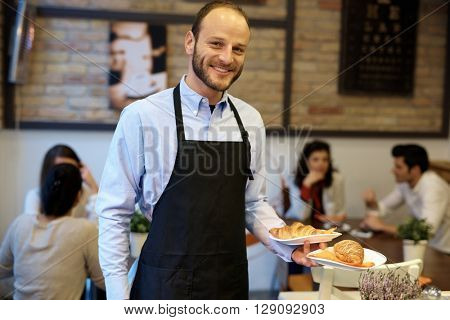 Portrait of happy waiter holding plates, serving guests.