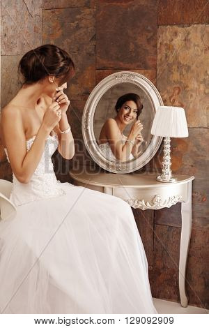 Beautiful young bride fixing knot of hair in mirror, smiling happy.