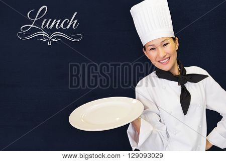 Smiling female cook holding empty plate in kitchen against navy blue