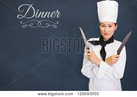 Confident female cook holding knives in kitchen against dinner message on a white background