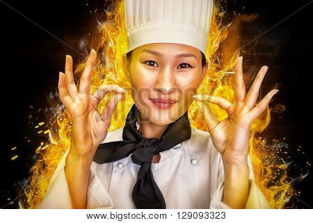 Closeup of a smiling female cook gesturing okay sign against dark background