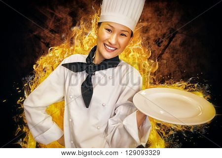 Smiling female cook holding empty plate in kitchen against shades of brown